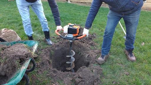 Tarière thermique, deux personnes créent un trou avec une tarière